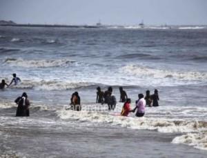 Tourist enjoying waves during high tide at Juhu beach in Mumbai.