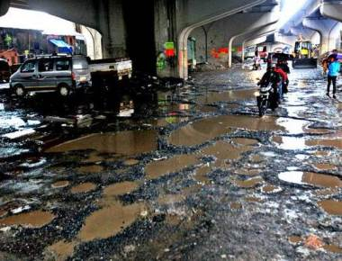 Rain pounds city; lakes brim over, roads crumble