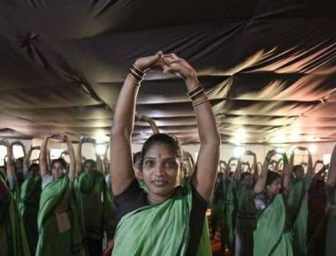 Women sweepers take a break from work to exercise, meditate